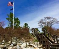 Schritte, die von der felsigen Küstenlinie zum Flaggenpfosten mit Flagge Vereinigter Staaten und Maine States führen lizenzfreies stockbild
