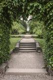 Schritte durch Bogen zu den formalen landschaftlich gestalteten Gärten Lizenzfreies Stockbild