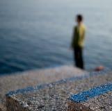 Schritte und einziger Mann, die heraus zum Meer schauen Stockfoto
