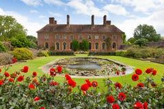 Schritten Haus Barrington Court nahe Ilminster Somerset England Großbritannien mit Lilienteichgarten und rote Dahlien im Sommer