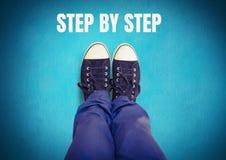 Schrittweiser Text und schwarze Schuhe auf Füßen mit blauem Hintergrund Stockbilder