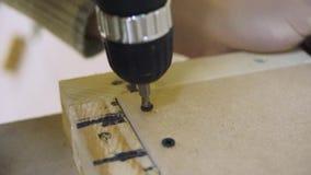 Schroevedraaier op een houten lijst, schroeven voorraad De schroevedraaier spint de schroef stock footage