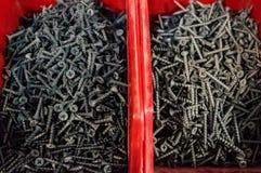 Schroeven, pennen en spijkers in rode dozen in de minimarkt voor verkoop Selectieve nadruk stock afbeeldingen