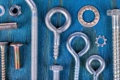 Schroevennoten en wasmachines van verschillende types en maatregelen op blauw stock foto