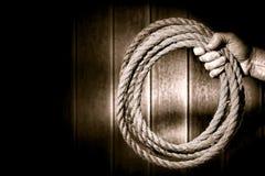 Schroffe Cowboy-Hand, die fest ein Ranching-Seil anhält stockbild