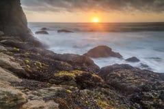 Schroffer Küstenliniensonnenuntergang über Gray Whale Cove State Beach lizenzfreies stockfoto