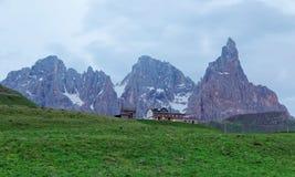 Schroffes Cimon-della Pala unter Spitzen von Pale di San Martino-Bergen mit einem Hotel auf gr?nem grasartigem H?gel in Passo Rol stockfotos