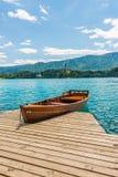 Schronienie i łódź na Krwawiącym jeziorze, Slovenia Drewniane łodzie na czystej błękitne wody Letni dzień blisko lasu i Alps zdjęcie royalty free