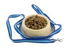 Schrotet Hundefutter in der braunen Plastikhundeschüssel und in der blauen Nylonleine Lizenzfreie Stockfotos