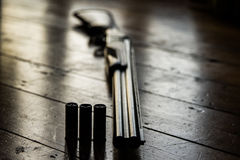 Schrotflinte lud mit Kugeln und Ersatzkugeln auf Bretterboden auf, Stockfotos