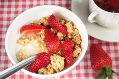Schüssel Getreide mit Erdbeeren und einer Tasse Tee Stockfoto