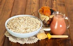 Schüssel mit Haferflocken, Krug Saft, Nüsse und Trockenfrüchte auf Hintergrunddunkelheitsholz Stockfoto