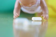 Schätzchen, das in Richtung zu einer verschütteten Pille kriecht Lizenzfreie Stockbilder