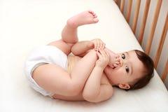 Schätzchen, das seine Zehen saugt! Stockbild