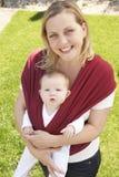 Schätzchen im Riemen mit Mutter draußen Stockfotografie