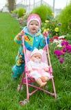 Schätzchen mit Puppe auf Weg. Lizenzfreie Stockfotos