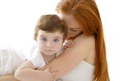 Schätzchen- und Redheadmutterumarmung auf Weiß Stockbilder