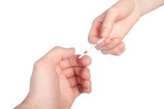 Schätzchenprüfung in der männlichen u. weiblichen Hand. Lizenzfreies Stockbild