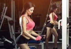 Schudnięcie, bodybuilder dziewczyna stoi przed lustrem w gym, robi ćwiczeniom Obrazy Stock