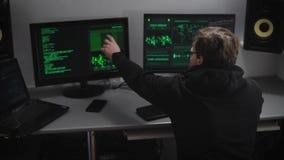 Schufthacker analysiert illegal erhaltene Daten bezüglich der Bildschirme für die Schaffung von Spions-Software Junger Mann in Gl stock footage