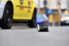 Schuh auf der Straße mit Autos im Hintergrund nach Unfall Stockbild