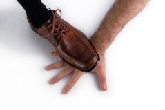Schuh, der einen überreichenweißhintergrund zerquetscht. Stockbild
