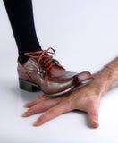 Schuh, der einen überreichenweißhintergrund zerquetscht Lizenzfreie Stockfotos