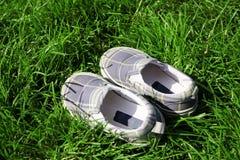 Schuh des Kindes in einem Gras Lizenzfreie Stockbilder