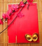 Schuh-förmiger Goldbarren (Yuan Bao) und Plum Flowers mit rotem Paket Stockfoto