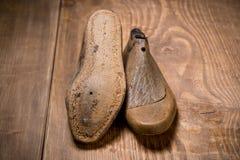 Schuh-Letzte auf dem braunen hölzernen Hintergrund Retro- Art Stockbild