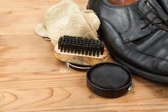 Schuhcreme mit Bürste, Stoff und abgenutzten Mannschuhen auf hölzernem platf Lizenzfreies Stockbild