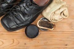 Schuhcreme mit Bürste, Stoff und abgenutzten Mannschuhen auf hölzernem platf Lizenzfreie Stockfotografie