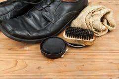 Schuhcreme mit Bürste, Stoff und abgenutzten Mannschuhen auf hölzernem platf Lizenzfreie Stockbilder