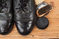 Schuhcreme mit Bürste, Stoff und abgenutzten Stiefeln auf hölzerner Plattform Lizenzfreie Stockfotos