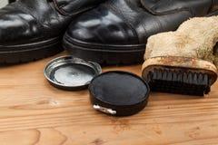 Schuhcreme mit Bürste, Stoff und abgenutzten Stiefeln auf hölzerner Plattform Stockfoto