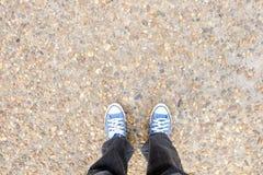 Schuhe auf felsigem Boden und schwarzen Jeans Stockfoto