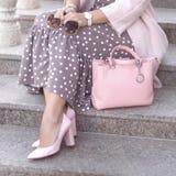 Schuhe auf Frauen ` s Bein rosa Schuhe, Tasche Sonnenbrille in der Handfrau Modedamenzubehör, Armbänder, Brillen stockfotos