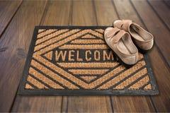 Schuhe auf neuer willkommener Fußmatte auf Bretterboden lizenzfreies stockfoto