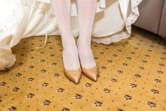Schuhe der goldenen Heirat auf Brautfüßen lizenzfreie stockfotos