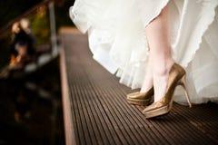 Schuhe der goldenen Heirat von der weißen gekleideten Braut stockfotografie