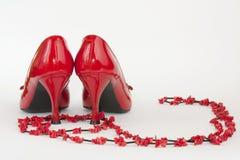 Schuhe der roten Dame mit Schmucksachen Stockbilder