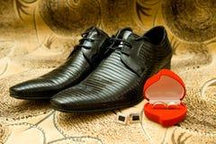 Schuhe des Bräutigams und Hochzeitsringe Stockbild