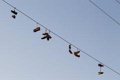 Schuhe, die auf einer elektrischen Leitung über der Straße baumeln Lizenzfreies Stockfoto