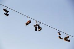 Schuhe, die auf einer elektrischen Leitung über der Straße baumeln Lizenzfreie Stockfotos