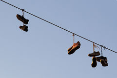 Schuhe, die auf einer elektrischen Leitung über der Straße baumeln Stockfotografie