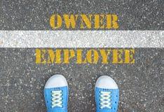 Schuhe, die an der Linie zwischen Angestelltem und Inhaber stehen Lizenzfreies Stockfoto