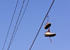 Schuhe, die von der Stromleitung baumeln lizenzfreies stockbild
