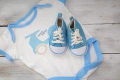 Schuhe für das Baby und Kleidung für einen Jungen auf einem weißen hölzernen BAC Stockbild