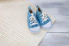 Schuhe für ein Baby und eine Decke auf einem hölzernen Hintergrund Stockfoto