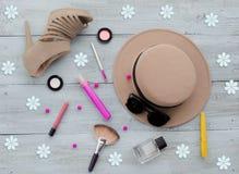 Schuhe, Hut, Sonnenbrille, Parfüm, Tinte, Lidschatten, Blumen, Lippenstift, Make-upbürste, erröten, Draufsicht über einen blauen  Stockbilder